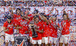 Houston guard DeJon Jarreau (3) holds the championship trophy as he stands with teammates following the team's win over Cincinnati an NCAA college basketball game in the final round of the American Athletic Conference men's tournament Sunday, March 14, 2021, in Fort Worth, Texas. (AP Photo/Ron Jenkins)