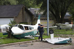 A law enforcement officer works at the site of the crash of a plane, in the front yard of a home Tuesday, July 28, 2020 in Houston. Two people were injured when the single-engine airplane crashed in a residential area early Tuesday, authorities said. The airplane hit a tree and landed in a front yard shortly before 2 a.m. (Brett Coomer/Houston Chronicle via AP)