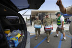 Members of the National Guard load water onto an SUV in the aftermath of an earthquake Sunday, July 7, 2019, outside Trona High School in Trona, Calif. (AP Photo/Marcio Jose Sanchez)