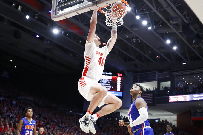Dayton's Chase Johnson (40) dunks over Houston Baptist's Zach Iyeyemi (34) during the first half of an NCAA college basketball game, Tuesday, Dec. 3, 2019, in Dayton, Ohio. (AP Photo/John Minchillo)