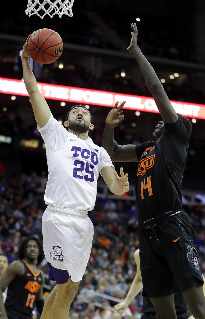 TCU's Alex Robinson (25) shoots under pressure from Oklahoma State's Yor Anei (14) during the second half of an NCAA college basketball game in the Big 12 men's tournament Wednesday, March 13, 2019, in Kansas City, Mo. TCU won 73-70. (AP Photo/Charlie Riedel)