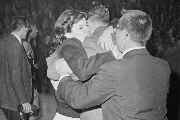 FILE - In this March 23, 1963, file photo, Kathy Ireland gives her father, Loyola coach George Ireland, a hug after they defeated Cincinnati 60-58 in overtime in the National Collegiate basketball finals in Louisville, Ky. Loyola Chicago guard Lucas Williamson is lending his voice and perspective to an upcoming documentary. The film is about the Ramblers' barrier-breaking team that won the 1963 NCAA championship. (AP Photo/File)