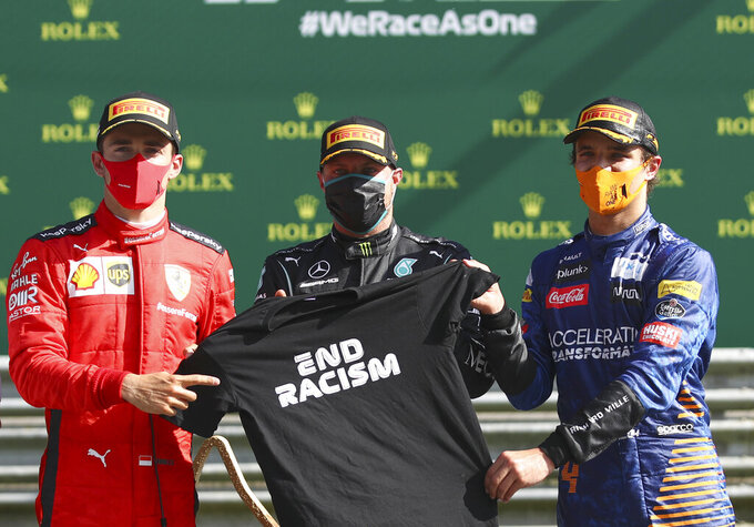 Race winner Mercedes driver Valtteri Bottas of Finland, centre, pose with second placed Ferrari driver Charles Leclerc of Monaco, left, and third placed Mclaren driver Lando Norris of Britain after the Austrian Formula One Grand Prix at the Red Bull Ring racetrack in Spielberg, Austria, Sunday, July 5, 2020. (Mark Thompson/Pool via AP)