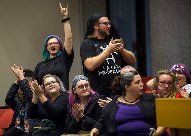 In this Dec. 4, 2019, photo opponents of the Bible Release Program show their support of one speaker's message during the public forum portion of the Knox County School Board Meeting held at the City-Council building in Knoxville, Tenn. (Brianna Paciorka/Knoxville News Sentinel via AP)