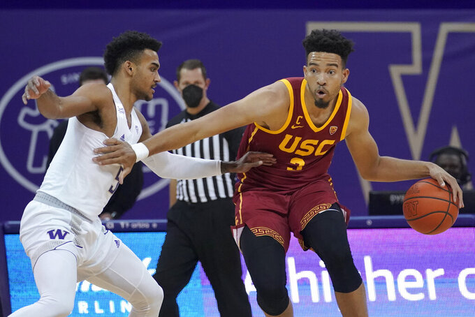 Southern California forward Isaiah Mobley, right, tries to drive around Washington guard Jamal Bey during the first half of an NCAA college basketball game Thursday, Feb. 11, 2021, in Seattle. (AP Photo/Ted S. Warren)