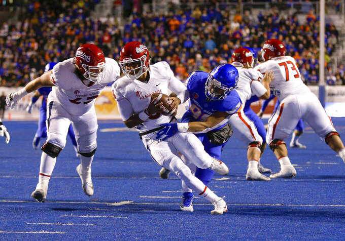 Fresno State quarterback Marcus McMaryion (6) tries to pull away from Boise State's Curtis Weaver (99) during the first half of an NCAA college football game Friday, Nov. 9, 2018, in Boise, Idaho. Weaver sacked McMaryion on the play. (AP Photo/Steve Conner)