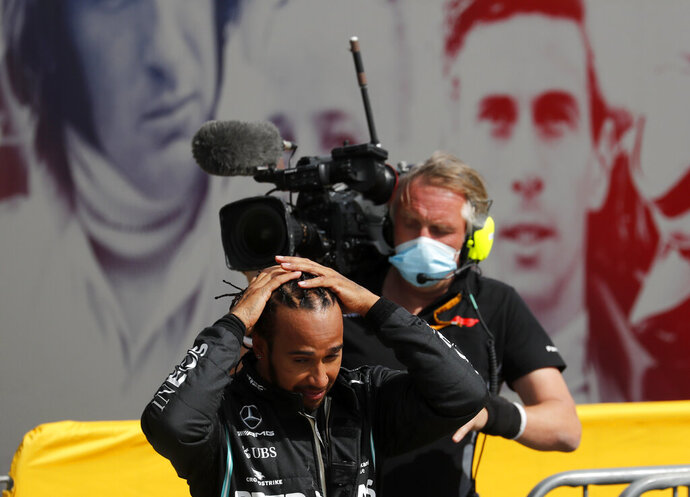 Race winner Mercedes driver Lewis Hamilton of Britain adjusts his hair after getting out of his car after the British Formula One Grand Prix at the Silverstone racetrack, Silverstone, England, Sunday, Aug. 2, 2020. (AP Photo/Frank Augstein, Pool)