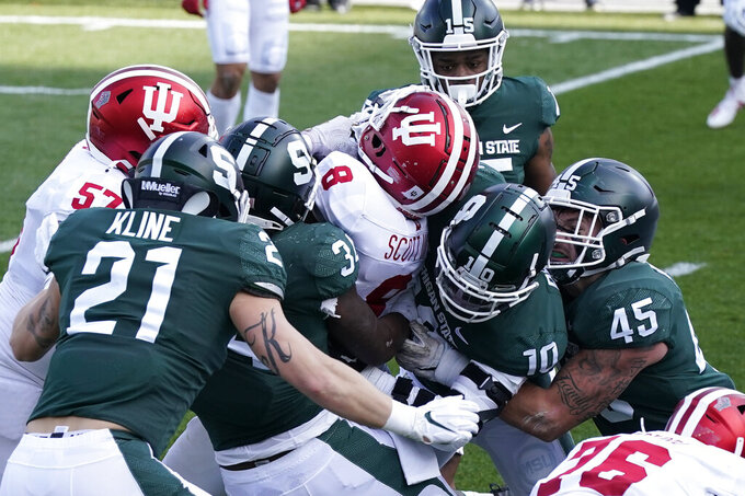 Indiana running back Stevie Scott III (8) is tackled by the Michigan State defense as he falls into the end zone for a touchdown during the first half of an NCAA college football game, Saturday, Nov. 14, 2020, in East Lansing, Mich. (AP Photo/Carlos Osorio)