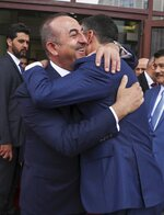 Turkey's Foreign Minister Mevlut Cavusoglu, left, embraces North Macedonia's Foreign Minister Nikola Dimitrov, right, prior to their meeting, in Skopje, North Macedonia, Tuesday, July 16, 2019. Cavusoglu on Tuesday downplayed as