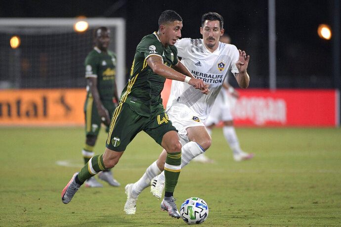 Portland Timbers midfielder Marvin Loria (44) controls the ball in front of LA Galaxy midfielder Sacha Kljestan during the first half of an MLS soccer match Monday, July 13, 2020, in Kissimmee, Fla. (AP Photo/Phelan M. Ebenhack)