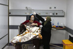 FILE - In this Friday, Jan. 22, 2021 file photo, a woman combs the hair of her sister, a COVID-19 patient, at the intensive care unit of the Rafik Hariri University Hospital in Beirut, Lebanon. As coronavirus vaccines trickle into some of the poorest countries in Asia, Africa and the Middle East, data suggest some women are consistently missing out, in another illustration of how the doses are being unevenly distributed around the world. (AP Photo/Bilal Hussein, file)