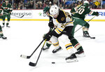 Boston Bruins' Par Lindholm (26), of Sweden, has the puck against Minnesota Wild's Mikko Koivu (9), of Finland, during the second period of an NHL hockey game Saturday, Feb. 1, 2020, in St. Paul, Minn. (AP Photo/Hannah Foslien)