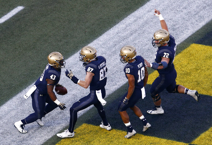 Navy fullback Nelson Smith, left, celebrates his touchdown with teammates Ryan Mitchell (87), Malcolm Perry (10) and Ford Higgins (72) in the first half of an NCAA college football game against Tulsa, Saturday, Nov. 17, 2018, in Annapolis, Md. (AP Photo/Patrick Semansky