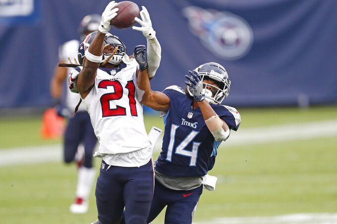 Houston Texans cornerback Bradley Roby (21) intercepts a pass intended for Tennessee Titans wide receiver Kalif Raymond (14) in the second half of an NFL football game Sunday, Oct. 18, 2020, in Nashville, Tenn. (AP Photo/Wade Payne)