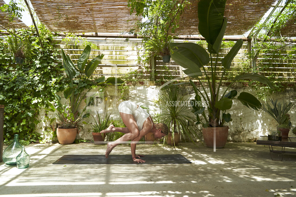 Mature woman balancing while doing yoga in garden