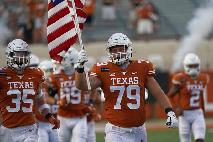 "Texas's Matt Frost (79) leads the team onto the field while carrying a U.S. flag and wearing a patch that says ""WeAreOne"" before the team's NCAA college football game against UTEP in Austin, Texas, Saturday, Sept. 12, 2020. (AP Photo/Chuck Burton)"