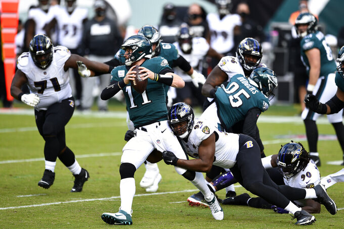 Philadelphia Eagles' Carson Wentz (11) is tackled by Baltimore Ravens' Calais Campbell (93) during the second half of an NFL football game, Sunday, Oct. 18, 2020, in Philadelphia. (AP Photo/Derik Hamilton)
