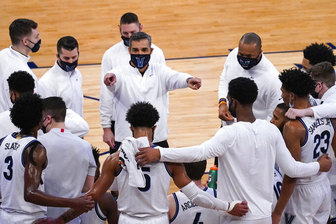 Villanova head coach Jay Wright, center, gives his team instruction during the first half of an NCAA college basketball game against Georgetown in the quarterfinals of the Big East conference tournament, Thursday, March 11, 2021, in New York. (AP Photo/Mary Altaffer)