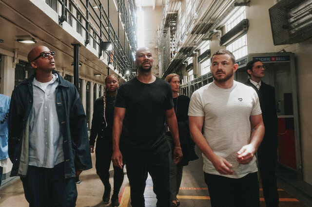 In this Aug. 2, 2018, photo, David Jassy, from left, front, a formerly incarcerated advocate, hip hop artist Common and Imagine Justice political advisor Michael Latt tour San Quentin State Prison in San Quentin, Calif. They are joined by Aun Madison, rear from left, Common's assistant, Jessica Jackson co-founder and National Director of #CUT50, Alex Gudich the Deputy Director of #CUT50. Common and Imagine Justice has launched a campaign with dozens of advocacy and activist groups calling attention to the threat coronavirus poses on millions of people jailed or imprisoned in the U.S. (JT McGlockton/Imagine Justice via AP)