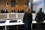 Dutch-Palestinian man Ismail Zeyada, originally from the Gaza Strip, right, and his lawyer Liesbeth Zegveld, rise as judges enter The Hague District Court, Netherlands, Wednesday, Jan. 29, 2020. The Dutch court is expected to rule on a case b brought by Zeyada on whether it has jurisdiction to take on a case in which he is seeking to sue Benny Gantz, former Chief of Staff of the Israel Defense Forces, and another Israeli military commander over their roles in an air strike that killed six members of his family. (AP Photo/Peter Dejong)