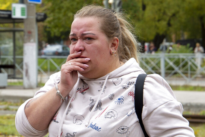 A woman reacts standing near the Perm State University in Perm, about 1,100 kilometers (700 miles) east of Moscow, Russia, Monday, Sept. 20, 2021. A gunman opened fire in a university in the Russian city of Perm on Monday morning, leaving at least eight people dead and others wounded, according to Russia's Investigative Committee. (AP Photo/Anastasia Yakovleva)
