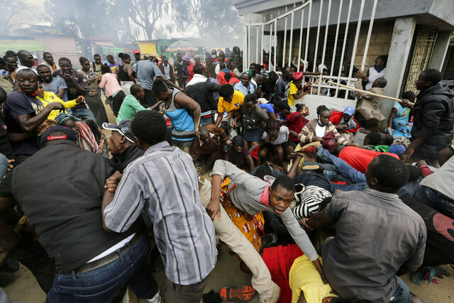 Residents desperate for a planned distribution of food for those suffering under Kenya's coronavirus-related movement restrictions push through a gate and create a stampede, causing police to fire tear gas and leaving several injured, at a district office in the Kibera slum, or informal settlement, of Nairobi, Friday, April 10, 2020. (AP Photo/Khalil Senosi)