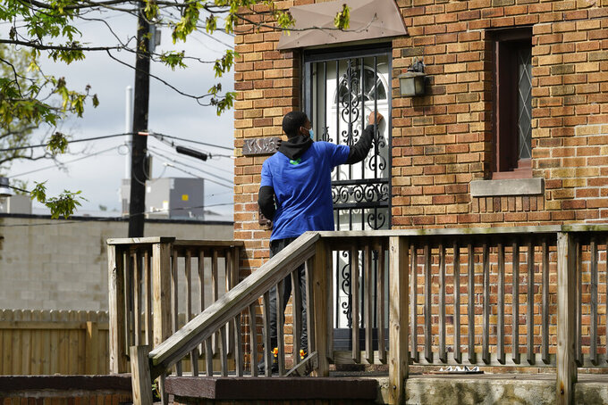 Sirgregory Allen knocks on a door before leaving a flyer on a home in Detroit, Tuesday, May 4, 2021. Officials are walking door-to-door to encourage residents of the majority Black city to get vaccinated against COVID-19 as the city's immunization rate lags well behind the rest of Michigan and the United States. (AP Photo/Paul Sancya)