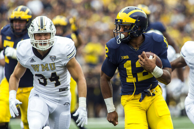 Michigan running back Chris Evans (12) rushes for a 27-yard touchdown as Western Michigan linebacker Alex Grace (34) chases in the first quarter of an NCAA college football game in Ann Arbor, Mich., Saturday, Sept. 8, 2018. (AP Photo/Tony Ding)