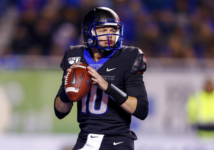 Boise State quarterback Chase Cord (10) looks for a receiver during the first half of the team's NCAA college football game against Wyoming on Saturday, Nov. 9, 2019, in Boise, Idaho. (AP Photo/Steve Conner)