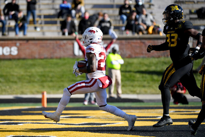 Arkansas running back Trelon Smith, left, scores on a touchdown run past Missouri linebacker Chad Bailey (33) during the second half of an NCAA college football game Saturday, Dec. 5, 2020, in Columbia, Mo. (AP Photo/L.G. Patterson)