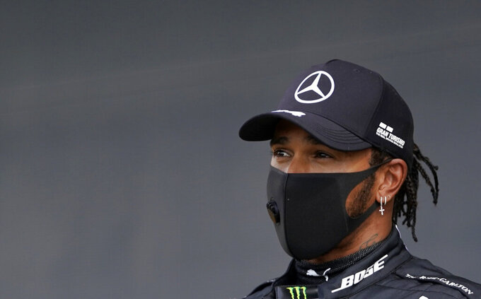 Mercedes driver Lewis Hamilton of Britain addresses the media after he clocked the fastest time during the qualifying session for the British Formula One Grand Prix at the Silverstone racetrack, Silverstone, England, Saturday, Aug. 1, 2020. The British Formula One Grand Prix will be held on Sunday. (Will Oliver/Poolvia AP)