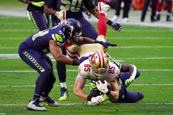 San Francisco 49ers tight end George Kittle (85) is hit by Seattle Seahawks safety Ugo Amadi and middle linebacker Bobby Wagner (54) during the first half of an NFL football game, Sunday, Jan. 3, 2021, in Glendale, Ariz. (AP Photo/Rick Scuteri)