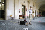 A woman with her dog leaves after voting at a polling station, in Rome, Sunday, Sept. 20, 2020. On Sunday and Monday Italians are called to vote nationwide in a referendum to confirm a historical change to the country's constitution to drastically reduce the number of Members of Parliament from 945 to 600. Eighteen million of Italian citizens will also vote on Sunday and Monday to renew local governors in seven regions, along with mayors in approximately 1,000 cities. (AP Photo/Andrew Medichini)