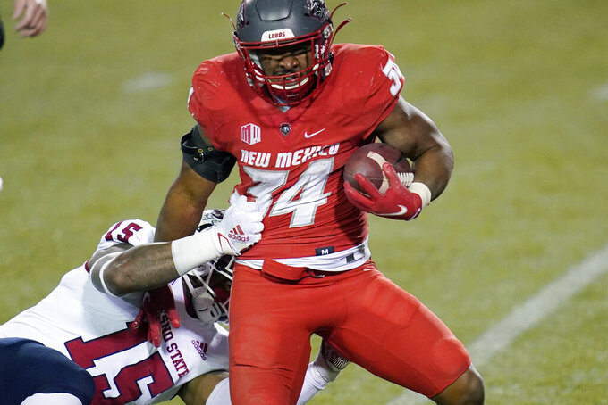 New Mexico running back Bobby Cole (34) runs for a gain against Fresno State linebacker Arron Mosby (15) during the second half of an NCAA college football game Saturday, Dec. 12, 2020, in Las Vegas. (AP Photo/John Locher)