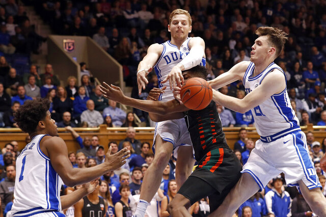 Miami forward Anthony Walker is blocked by Duke forward Jack White and forward Matthew Hurt (21) while center Vernon Carey Jr. (1) looks on during the first half of an NCAA college basketball game in Durham, N.C., Tuesday, Jan. 21, 2020. (AP Photo/Gerry Broome)