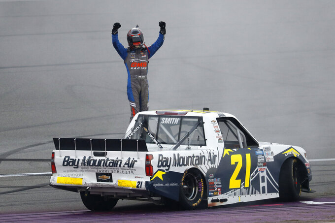 Zane Smith celebrates his victory after a NASCAR Truck Series auto race at Michigan International Speedway in Brooklyn, Mich., Friday, Aug. 7, 2020. (AP Photo/Paul Sancya)