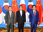 CORRECTS POSITIONS - Chinese Premier Li Keqiang, center, Japan's Prime Minister Shinzo Abe, right, and South Korean President Moon Jae-in, left, pose for a group photo before the trilateral meeting between China, South Korea and Japan in Chengdu, southwest China's Sichuan province Tuesday, Dec. 24, 2019. (Yoshitaka Sugawara/Kyodo News via AP)
