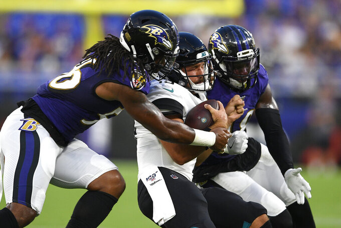 Jacksonville Jaguars quarterback Gardner Minshew, is sandwiched between Baltimore Ravens linebacker Tim Williams, left, and inside linebacker Patrick Onwuasor during the first half of an NFL football preseason game Thursday, Aug. 8, 2019, in Baltimore. (AP Photo/Nick Wass)