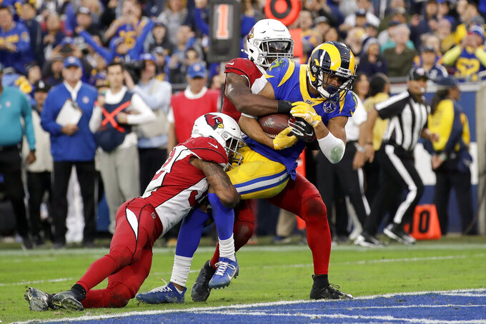 Los Angeles Rams wide receiver Robert Woods, middle, scores between Arizona Cardinals strong safety Budda Baker, left, and cornerback Patrick Peterson during second half of an NFL football game Sunday, Dec. 29, 2019, in Los Angeles. (AP Photo/Marcio Jose Sanchez)