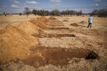A worker walks past a freshly-dug graves at the Honingnestkrans Cemetery, North of Pretoria, South Africa, Thursday, July 9, 2020. The Africa Centers for Disease Control and Prevention says the coronavirus pandemic on the continent is reaching