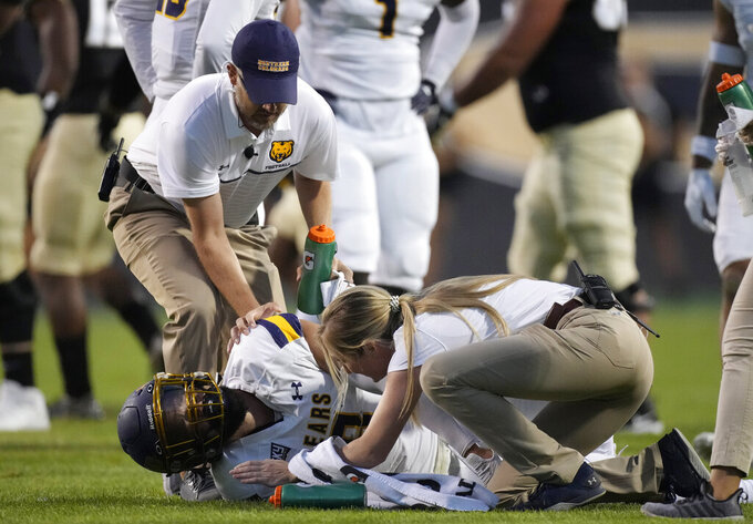 Trainers tend to Northern Colorado defensive back Jordan Knapke after he was injured while tackling Colorado quarterback Brendon Lewis in the first half of an NCAA college football game Friday, Sept. 3, 2021, in Boulder, Colo. (AP Photo/David Zalubowski)