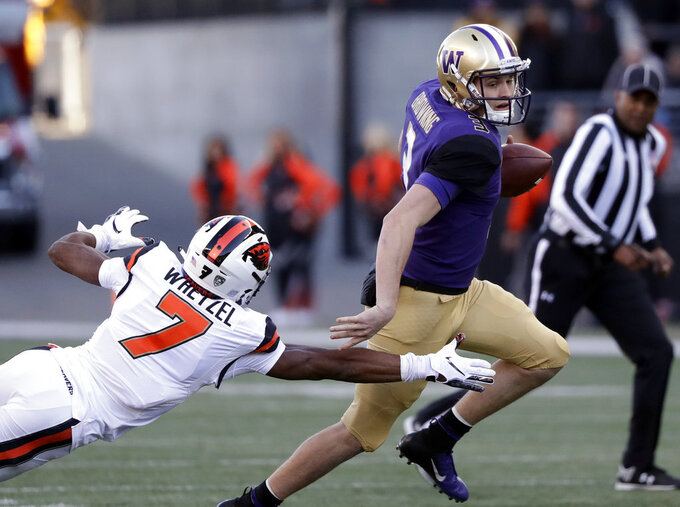 Washington quarterback Jake Browning, right, tries to elude Oregon State's Kee Whetzel in the first half of an NCAA college football game Saturday, Nov. 17, 2018, in Seattle. (AP Photo/Elaine Thompson)