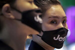 Receptionists wearing face masks carrying the car brand to help curb the spread of the coronavirus at the Auto China 2020 show in Beijing, Sunday, Sept. 27, 2020. Auto China 2020, postponed from March, is the first major trade show for any industry since the pandemic began as automakers are looking to China, the first major economy to start recovering from the coronavirus pandemic, to drive sales growth and reverse multibillion-dollar losses. (AP Photo/Andy Wong)
