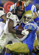 UCLA running back Demetric Felton (10) is tackled by Oregon State linebacker Shemar Smith (41) during the second half of an NCAA college football game Saturday, Oct. 5, 2019, in Pasadena, Calif. (AP Photo/Marcio Jose Sanchez)