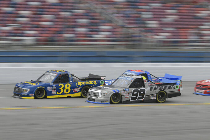 Ben Rhodes (99) and Todd Gilliland (38) run side-by-side during the NASCAR Truck Series auto race Saturday, Oct. 2, 2021, in Talladega, Ala. (AP Photo/John Amis)