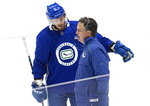 Vancouver Canucks' J.T. Miller (9) talks to head coach Travis Green during the NHL hockey team's training camp in Vancouver, British Columbia, Saturday, July 25, 2020. (Darryl Dyck/The Canadian Press via AP)