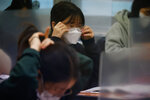 A student adjusts her mask ahead of the annual college entrance examination amid the coronavirus pandemic at an exam hall in Seoul, South Korea, Thursday, Dec. 3, 2020. South Korean officials are urging people to remain at home if possible and cancel gatherings as about half a million students prepare for a crucial national college exam. (Kim Hong-Ji/Pool Photo via AP)