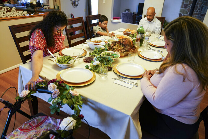 Vivian Zayas holds onto the walker once belonging to her recently deceased mother Ana Martinez while her family prays before Thanksgiving dinner, Thursday, Nov. 26, 2020, in Deer Park, N.Y. Ana Martinez died at 78 on April 1 while recovering at a nursing home from a knee replacement. (AP Photo/John Minchillo)
