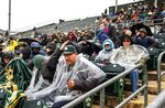 Fans at Hohokam Stadium try to cover up as rain settles in and ends up canceling a spring training baseball game between The Seattle Mariners and the Oakland Athletics after 1-1/2 innings Thursday, Feb. 21, 2019, in Mesa, Ariz. (Dean Rutz/The Seattle Times via AP)