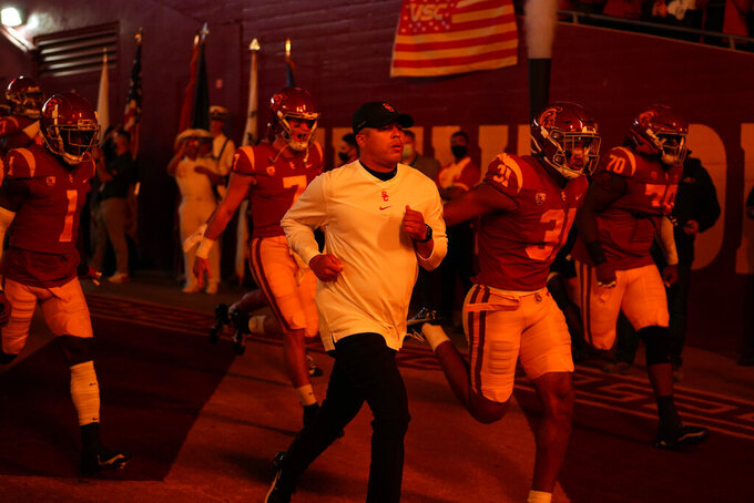 Southern California head coach Donte Williams, center, enters the field with his team before an NCAA college football game against Oregon State, Saturday, Sept. 25, 2021, in Los Angeles. (AP Photo/Marcio Jose Sanchez)